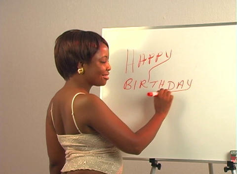 "Sexy woman writes ""Happy Birthday Handsome"" on a white board Stock Video Footage"