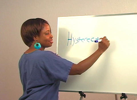 "Beautiful Nurse Writes ""Hysterectomy"" on a White Board Stock Video Footage"