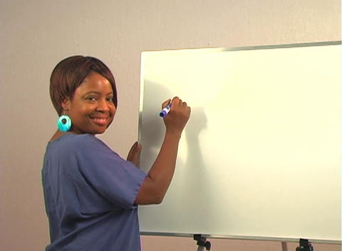 "Beautiful Nurse Writes ""Hysteroscopy"" on a White Board Stock Video Footage"