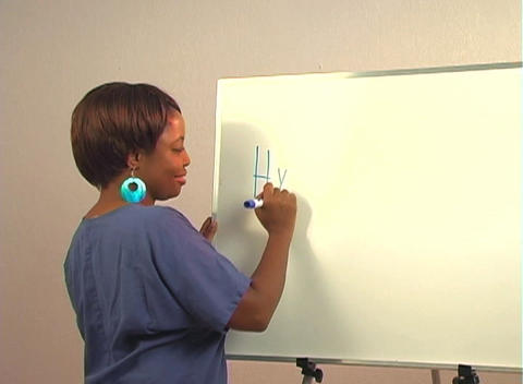 "Beautiful Nurse Writes ""Hysteroscopy"" on a White Board Footage"