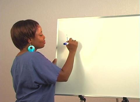 "Beautiful Nurse Writes ""Inguinal Hernia"" on a White Board Stock Video Footage"