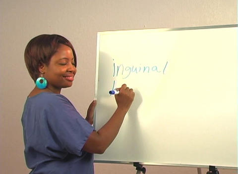 "Beautiful Nurse Writes ""Inguinal Hernia"" on a White Board Footage"