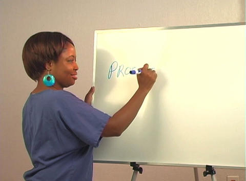 "Beautiful Nurse Writes ""Prostatectomy"" on a White Board Stock Video Footage"