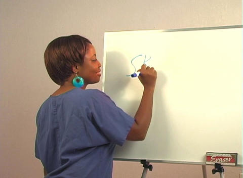 "Beautiful Nurse Writes ""Skin Graft"" on a White Board Stock Video Footage"