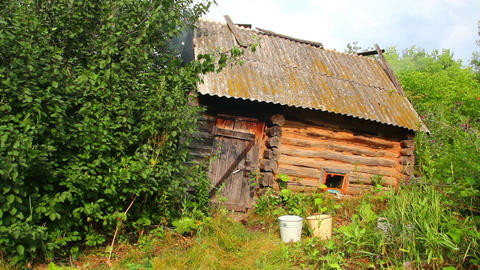 old obsolete russian bath-house in lush foliage Stock Video Footage