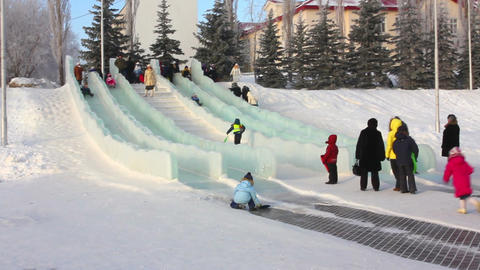 Children slide down on icy hill in winter Stock Video Footage