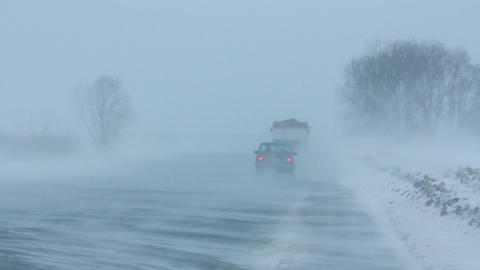 cars on winter road at blizzard Stock Video Footage