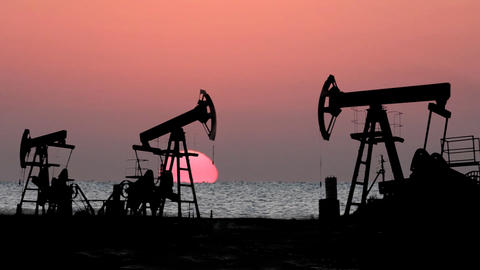 working oil pumps silhouette against sunrise Stock Video Footage