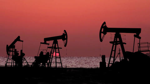 working oil pumps silhouette against timelapse sun Stock Video Footage