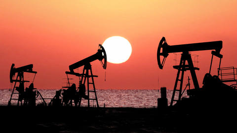 working oil pumps silhouette against timelapse sun Footage