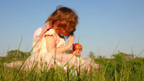 little girl eating apple on meadow Footage