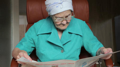 old woman sitting on chair and reading newspaper Stock Video Footage