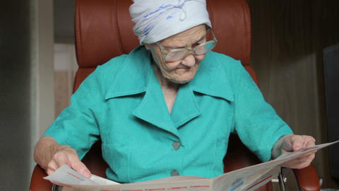 old woman sitting on chair and reading newspaper Footage