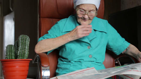 old woman reading and turn over pages of newspaper Footage
