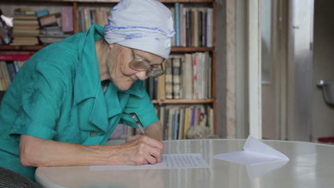 old woman in glasses writing letter Stock Video Footage