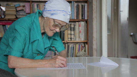 old woman in glasses writing letter Footage