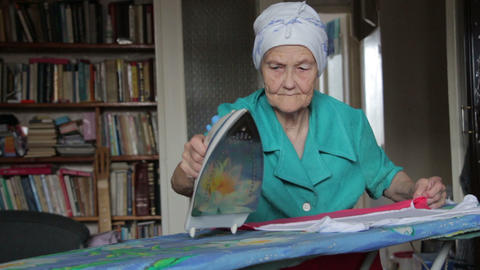 old woman at ironing board Stock Video Footage