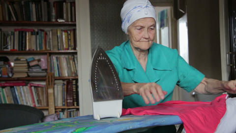 old woman at ironing board Footage