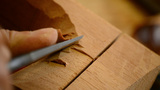 Craftsman with chisel working in wood close up Footage