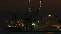 Unloading cargo ship at night 1 Stock Video Footage