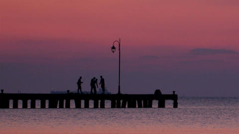 People on a pier at sunset Stock Video Footage
