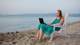 Woman relaxing at the beach with her laptop talkin Stock Video Footage