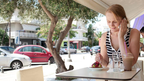 Woman sitting at a cafeteria talking on a mobile Stock Video Footage