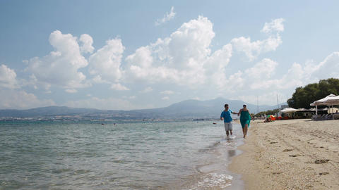 Young couple running along a beach Stock Video Footage