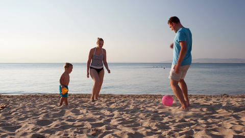 Young family playing football on the beach Stock Video Footage