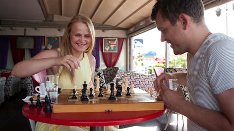 Smiling couple playing a game of chess Footage