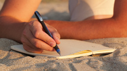 Man writing in his diary at the beach Stock Video Footage