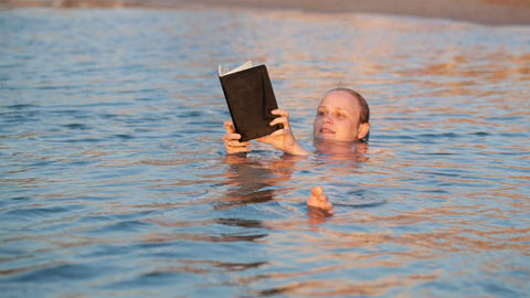 Woman smiling as she reads a book while swimming Footage