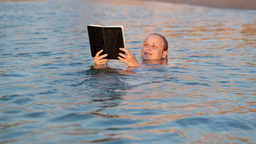 Woman smiling as she reads a book while swimming Stock Video Footage