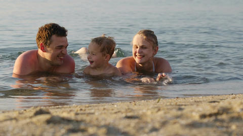 Laughing little boy with his parents at the sea Stock Video Footage