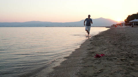 Man running along a tropical beach Stock Video Footage