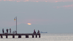 People relaxing on a pier at sunset. Ship is passi Stock Video Footage