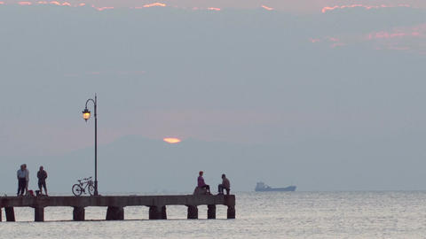 People relaxing on a pier at sunset. Ship is passi Footage