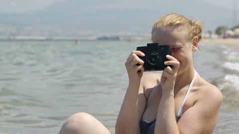 Smiling woman taking a photo at the seaside with h Stock Video Footage