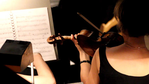 woman from behind playing on violin in orchestra Stock Video Footage