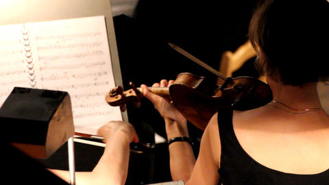woman from behind playing on violin in orchestra Footage