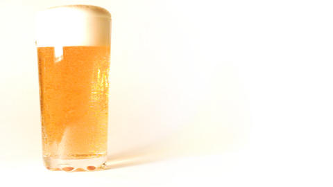 beer is poured into a glass on white background Stock Video Footage