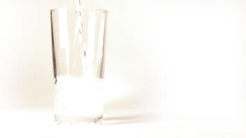 mineral water is poured into a glass on white back Stock Video Footage