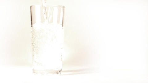 mineral water is poured into a glass on white back Footage
