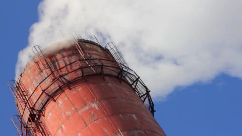 factory chimney with smoke under blue sky - timela Footage