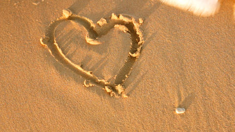sea wave erases drawing hearts with sand Stock Video Footage