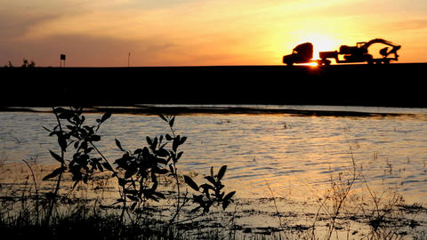 Lake and cars silhouettes on road against sunset Stock Video Footage