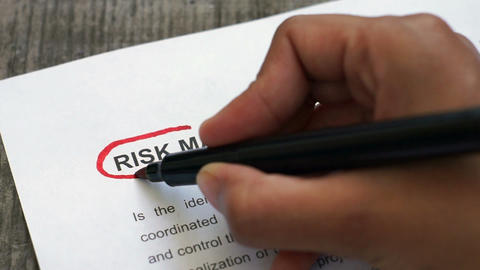 Circling Risk Management with a red marker Stock Video Footage