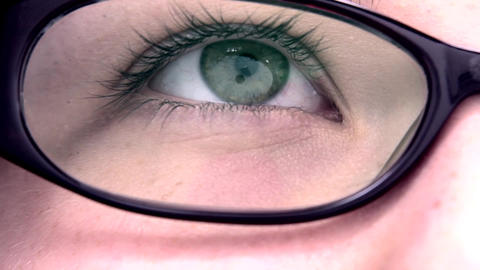 Extreme Close Up Of An Reading Eye Through The Gla stock footage