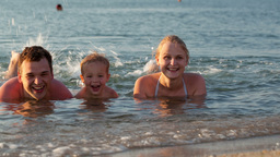 Young family splashing in the sea Stock Video Footage