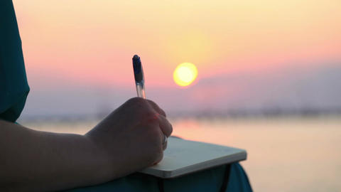 Woman writing in her diary at sunset Stock Video Footage
